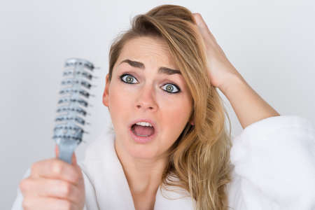 beautiful women: Worried Woman Suffering From Hairloss Looking At Comb