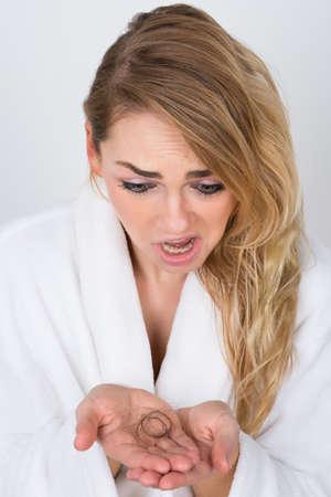 calvicie: Retrato de una sacudida eléctrica Mujer que sostiene la pérdida del pelo Foto de archivo