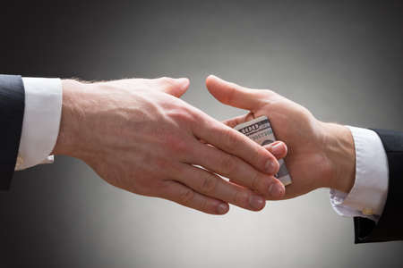 lend a hand: Close-up Of Businessman Hand Giving Bribe To Other Businessperson Stock Photo