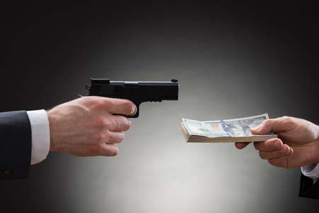 Close-up Of Businessman Hand Giving Money To The Businessperson With Gun photo