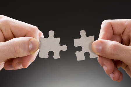 two piece: Close-up Of Hands Holding Jigsaw Pieces On Grey Background
