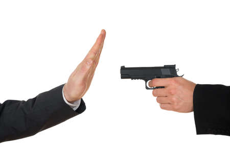 stringent: Businessman Hand With Gun Pointing Towards Businessperson Gesturing Stop Sign Over White Background Stock Photo