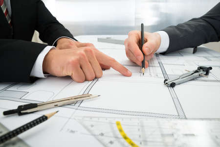 planning: Close-up Of Two Architects Planning Project On Blueprint Stock Photo
