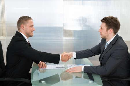 entrevista de trabajo: Dos hombre de negocios joven feliz que sacude Uno A Manos