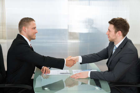 job opening: Two Young Happy Businessman Shaking Each Other Hands Stock Photo