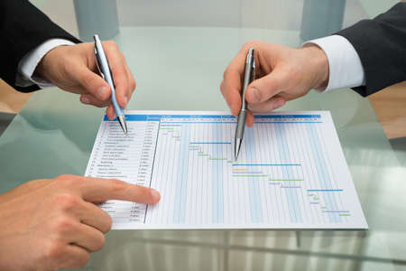 Close-up Of Two Businessman With Gantt Diagram At Desk 写真素材