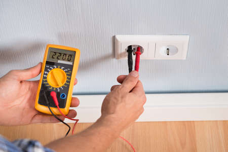 metering: Close-up Of Person Hand Metering Socket Voltage With Digital Multimeter