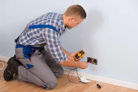 strom: Männlich Elektriker Prüfen von Stromspannung für Sockel mit Multimeter In House Lizenzfreie Bilder