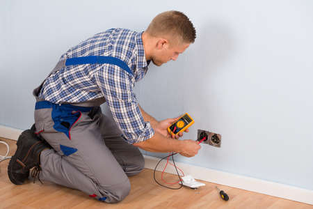 manual test equipment: Male Electrician Checking Voltage Of Socket With Multimeter In House