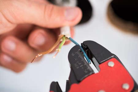 elektrizit u00e4t: Nahaufnahme Der Elektriker Hände entkleiden Elektrische Leitungen für Wandsteckdose Lizenzfreie Bilder