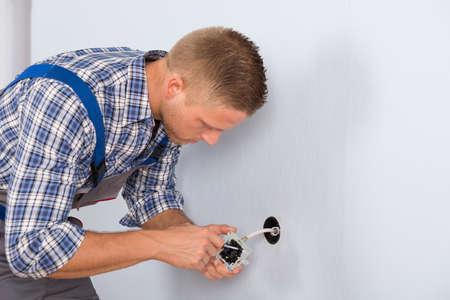 하우스에서 전기 소켓을 설치하는 젊은 전기 기사 스톡 콘텐츠