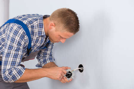 socket outlet: Young Electrician Installing Electrical Socket On Wall In House Stock Photo