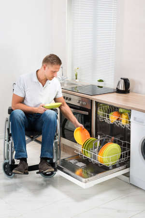 household accident: Young Disabled Man Sitting On Wheelchair Working In Kitchen Stock Photo