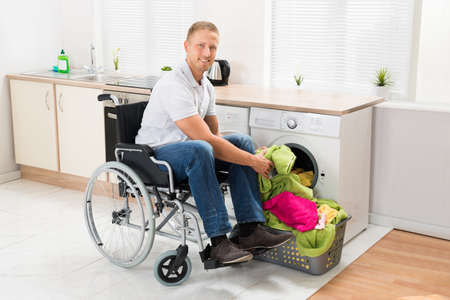 household accident: Young Happy Man On Wheelchair Putting Clothes Into The Washing Machine