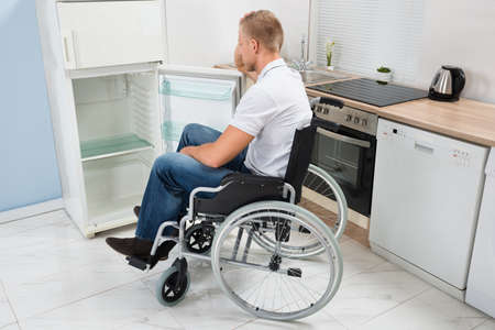 household accident: Disabled Man On Wheelchair Look Into An Empty Refrigerator Stock Photo