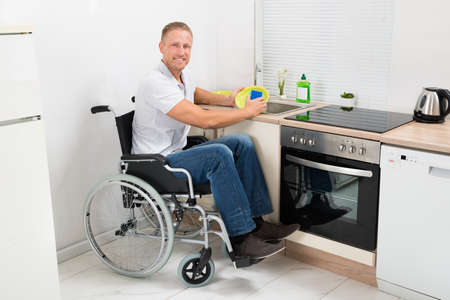 household accident: Young Happy Disabled Man On Wheelchair Washing Dishes
