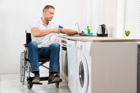 handicapped: Young Handicapped Man On Wheelchair Cleaning Induction Stove