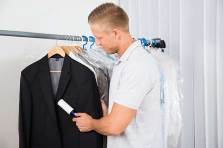 dry cleaner: Young Man Cleaning Dust Of Coat With Lint Roller In Clothing Store