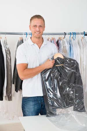 productos de limpieza: Joven Hombre Feliz Escudo Sosteniendo En tintorería tienda Foto de archivo