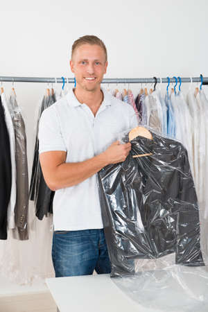 dry cleaning: Young Happy Man Holding Coat In Dry Cleaning Store Stock Photo