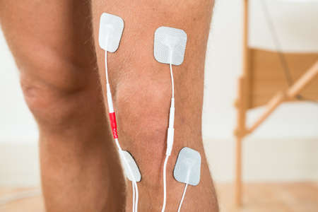 stimulator: Close-up Of Person Legs With Electrostimulator Electrodes On Knee