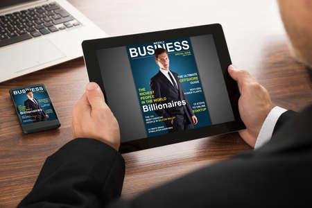 Close-up van een zakenman lezen van Online Magazine op digitale tablet en mobiele telefoon