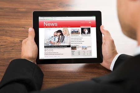 디지털 태블릿에서 온라인 뉴스를 읽고 사업가의 근접 스톡 콘텐츠