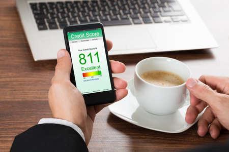 informe: Primer plano de un empresario Comprobación de puntuación de crédito en línea en el teléfono celular mientras que el café