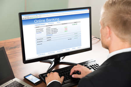 transaction: Close-up Of A Businessman Using Online Banking Service On Computer At Office Stock Photo