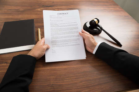 divorce court: Close-up Of Judge Holding Contract Paper At Desk Stock Photo