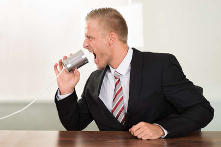 tin can telephone: Young Businessman Screaming In Tin Cans Phone At Desk Stock Photo