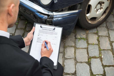 damaged car: Close-up Of A Man Filling Insurance Form Near Damaged Car Stock Photo