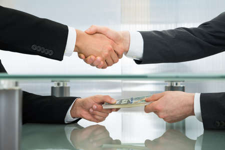Close-up Of Businessman With Money Handshaking With His Business Partner