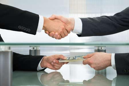 corrupcion: Primer plano del hombre de negocios con el dinero del apretón de manos con su socio de negocios