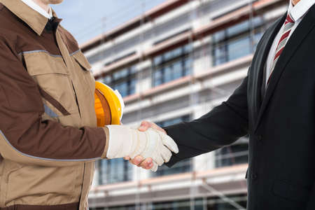 hat project: Close-up Of A Architect Wearing Glove Shaking Hand With Businessman