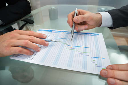 gantt: Close-up Of Two Businessman With Gantt Diagram At Desk Stock Photo