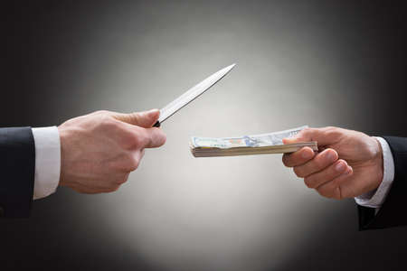 money hand: Close-up Of Businessman Hand Giving Money To The Businessperson With Sharp Knife