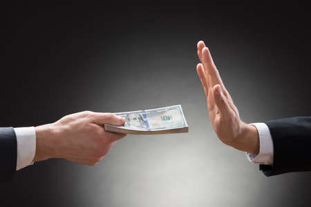 not give: Close-up Of Businessman Hand Rejecting The Money Offered By Other Businessman Stock Photo