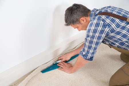 carpet floor: Close-up Of A Craftsman Fitting Carpet On Floor