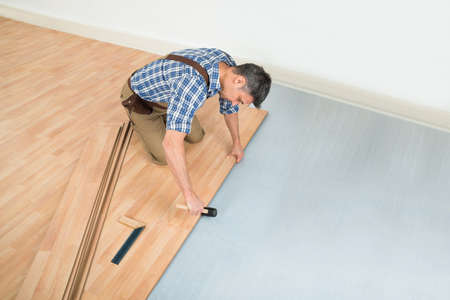 Carpenter Installing New Laminated Wooden Floor At Home Standard-Bild
