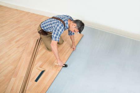 Carpenter Installing New Laminated Wooden Floor At Home Foto de archivo