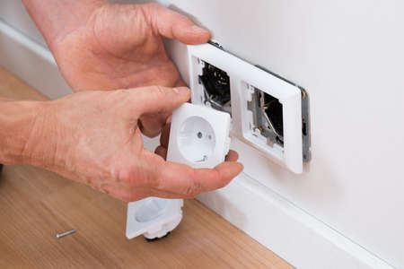 mounting: Close-up Of A Technician Adjusting Socket On Wall Stock Photo