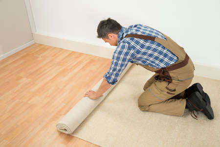 kneeling man: Male Worker Unrolling Carpet On Floor At Home