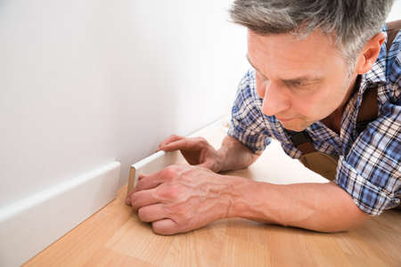 skirting: Close-up Of A Carpenter Leaning On Floor Applying Skirting On Wall Stock Photo