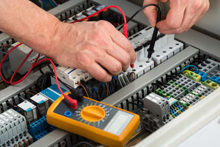 ingenieria elÉctrica: Primer Plano De Un Hombre Electricista Comprobación del fusible Con multímetro Foto de archivo