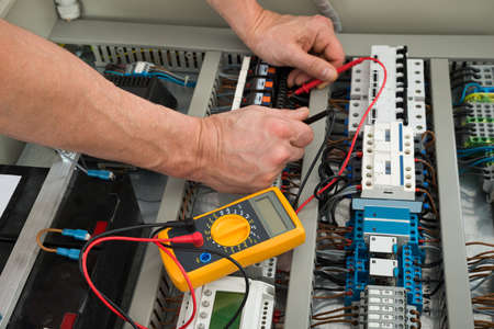manual test equipment: Close-up Of A Electrician Checking Fuse Box With Multimeter