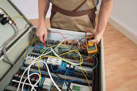multimeter: Close-up Of A Electrician Checking Fuse Box With Multimeter