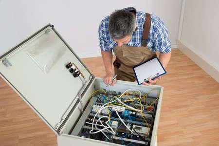 contador electrico: Electricista Mirando a la caja de fusibles que sostienen el sujetapapeles Foto de archivo