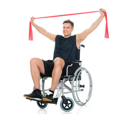 Wheel chair: Disabled Man On Wheelchair Exercising With Resistance Band Over White Background