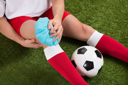 sports injury: Close-up Of A Soccer Player Icing Knee With Ice Pack On Field